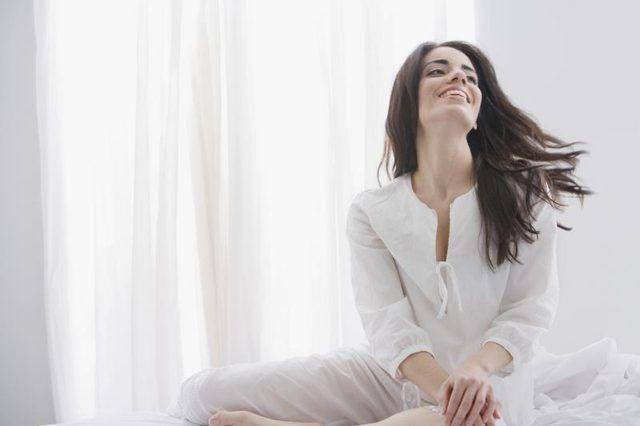 Una mujer feliz está sonriendo en su habitación.