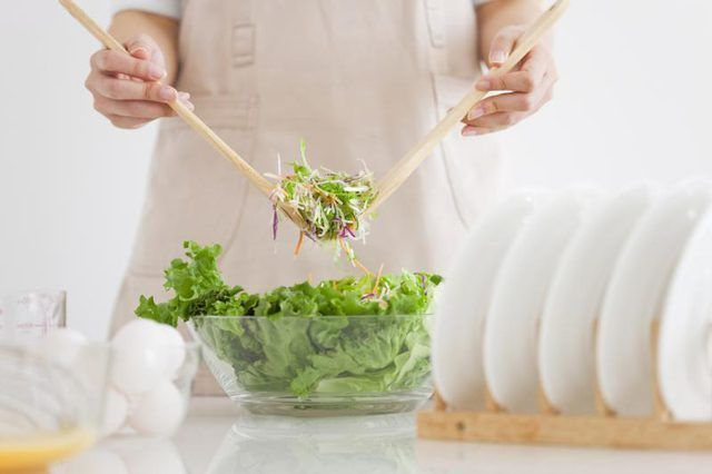 Una mujer es scooping ensalada en un tazón.