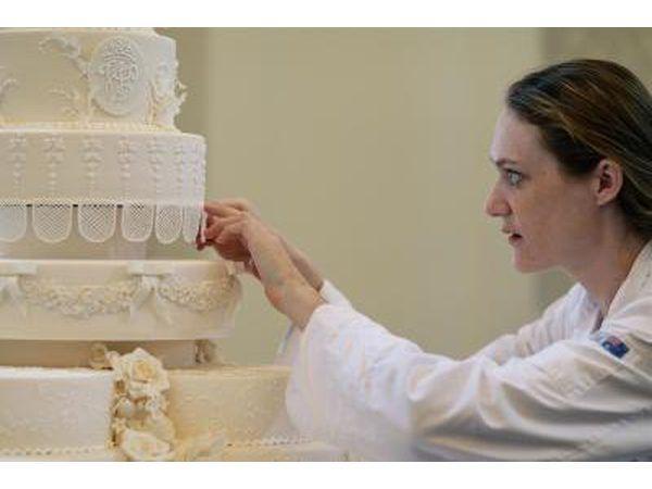 Panadero trabaja en toques finales a la torta de boda