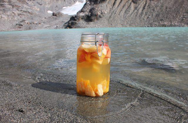 Una gran frasco de conservas de frutas de sangría siendo enfriado por la orilla de un lago alpino.