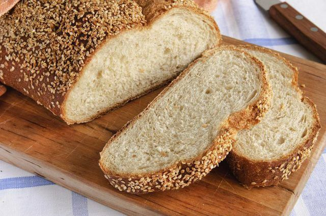 En rodajas hogaza de pan en la tabla de cortar.