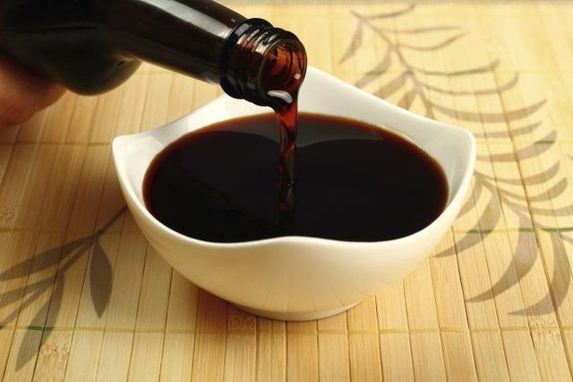 Primer plano de salsa de soja que se vierte en un recipiente pequeño.