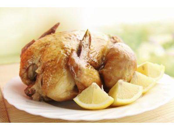 Un pollo asado en un plato con rodajas de limón fresco.