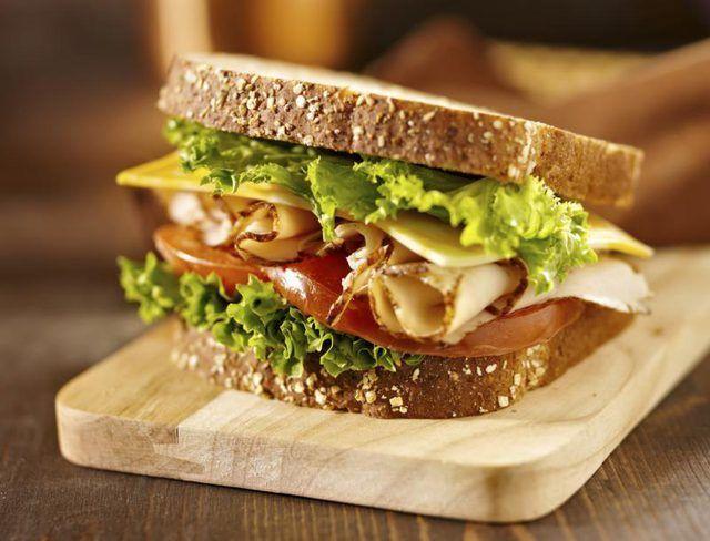 Un sándwich de pavo con lechuga, queso y tomate en un pan de grano entero.