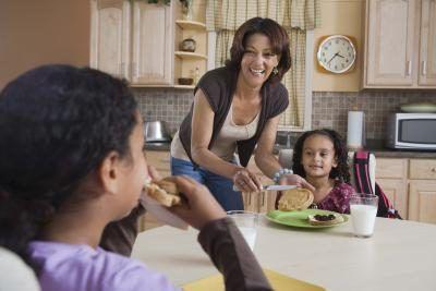 Hijas de la madre alimenta el desayuno en la mesa