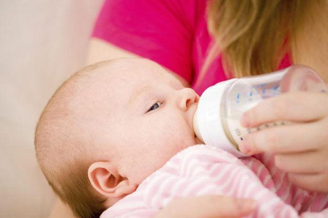 Primer plano del ser recién nacido alimentado con biberón.
