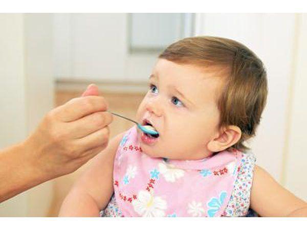 Niño de ser alimentados con cuchara en la silla alta.