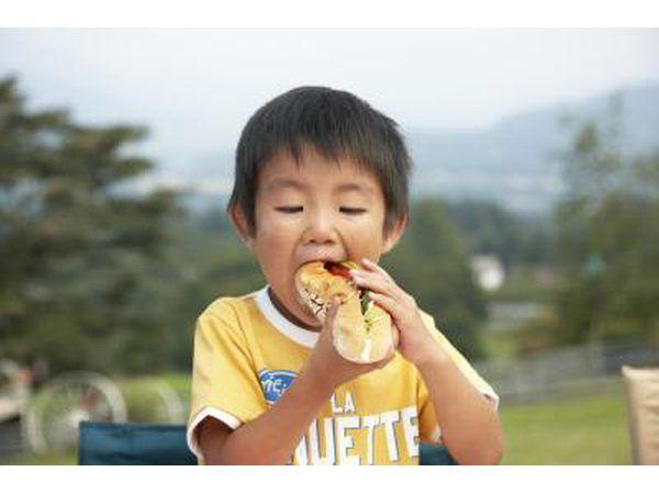 muchacho joven que come un perrito caliente.
