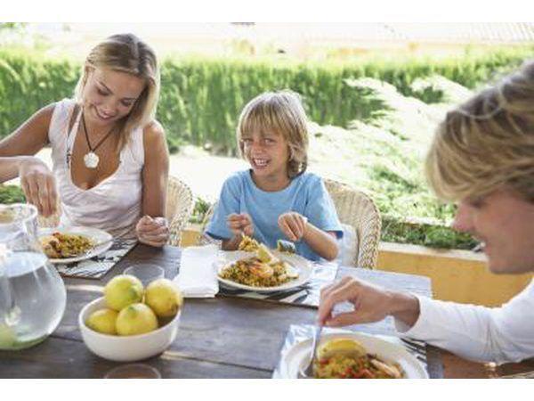 Muchacho que come en la mesa al aire libre con los padres