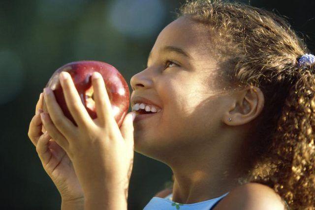 Chica joven que sostiene una manzana.