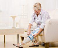 Una mujer mayor en su casa poniendo en una rodillera.