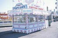 vendedores de comida de carnaval venden artículos tales como palomitas de maíz y algodón de azúcar.