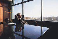 ejecutivo de negocios que se relaja y mirando por una ventana de la oficina.
