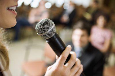 Mujer que habla en el micrófono a la audiencia