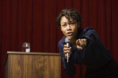 Mujer que llama miembro de la audiencia en el escenario