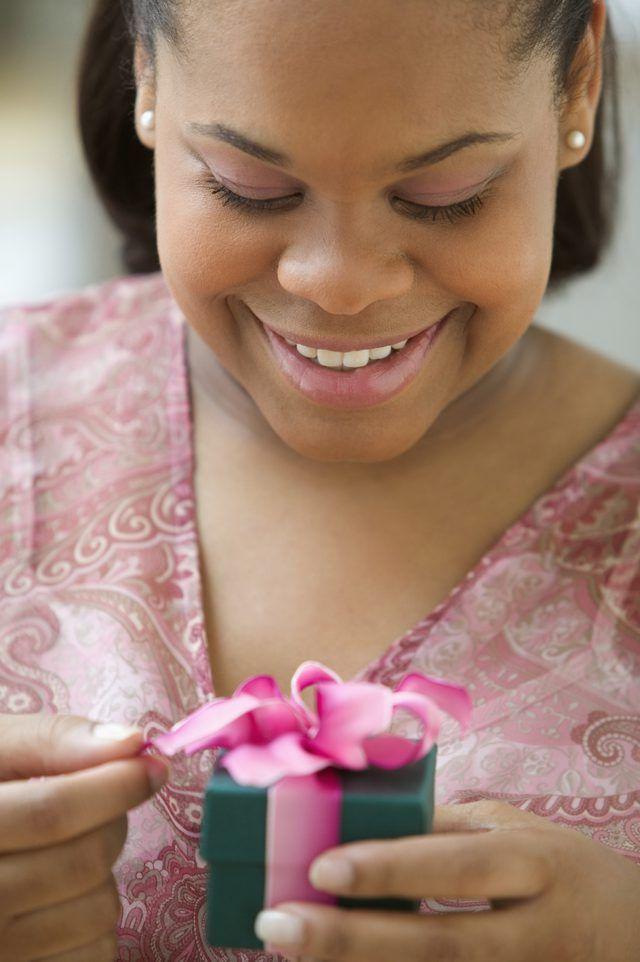 Una mujer que abre una pequeña caja de regalo.