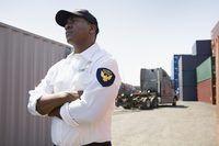 Los agentes de seguridad protegen los contenedores de transporte y la pantalla en instalaciones portuarias.