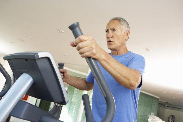 Un hombre maduro que está utilizando la máquina elíptica en el gimnasio.