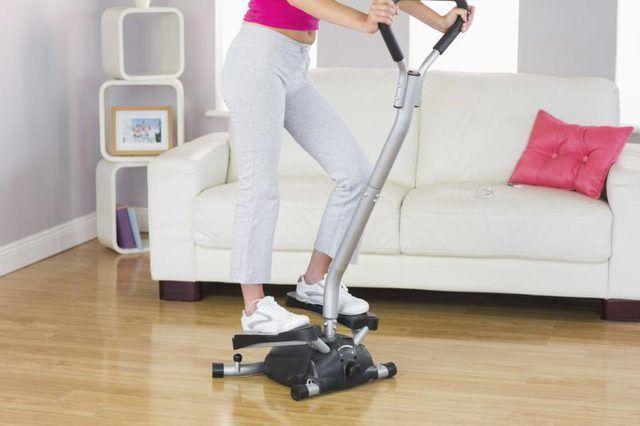 Una mujer está entrenando en una máquina de paso.