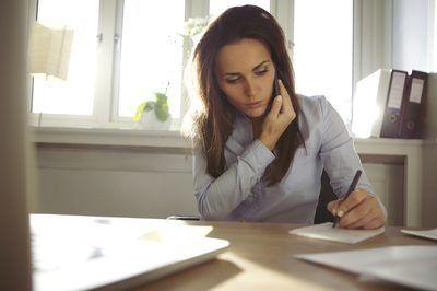 Mujer que toma notas con la pluma, mientras que en el teléfono