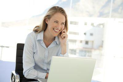 Mujer con ordenador portátil mientras en el teléfono