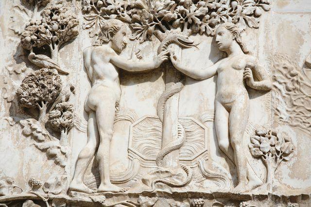 Un primer plano de una escultura en relieve de Adán y Eva sostiene la serpiente en el jardín.