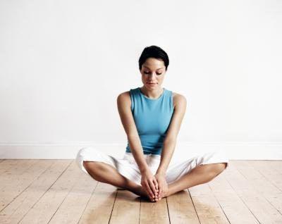 Mujer sentada en una pose de yoga en un piso de madera.