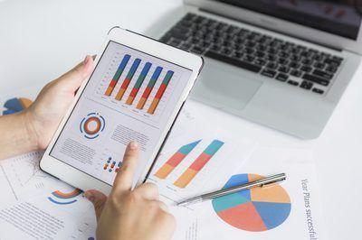 Hombre de negocios que mira a los informes de ingresos en una tableta de ordenador.