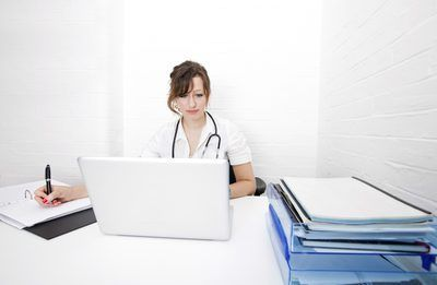 Un médico en su escritorio la preparación de documentos médicos para la facturación.