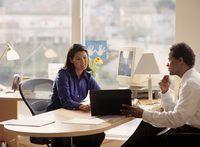 Un gerente y el empleado tienen una discusión en un escritorio de oficina.