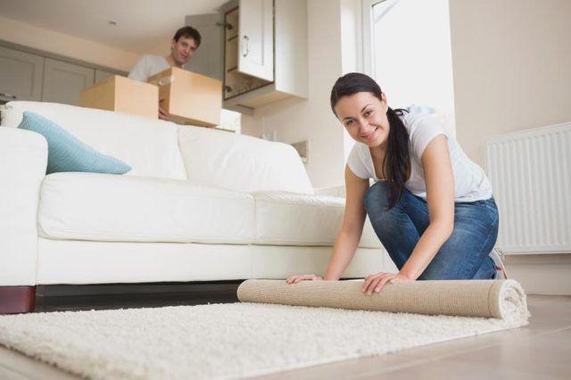 Una mujer desenrollar una alfombra delante de un sofá de dos plazas.