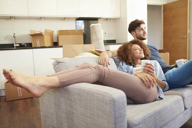 Un par que toma un descanso para tomar café en el sofá.