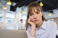 Una mujer deprimida sentado en una oficina moderna